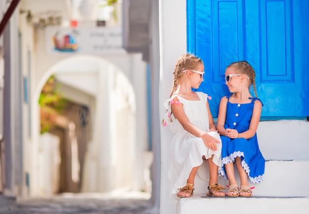 Kleine glückliche mädchen in den kleidern an der straße des typischen griechischen traditionellen dorfs mit weißen wänden und bunten türen auf mykonos-insel, in griechenland