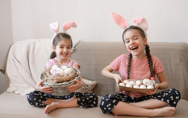 Kleine glückliche schwestern mit hasenohren, mit ostereiern