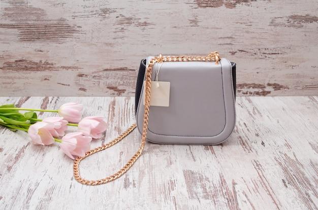 Kleine graue handtasche mit einem preis auf einem hölzernen hintergrund, rosa tulpen.