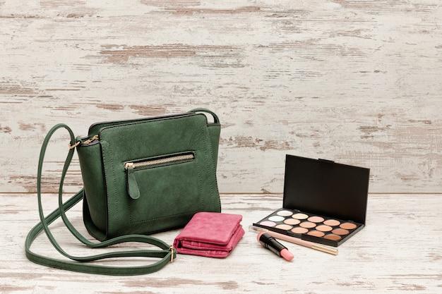 Kleine grüne damenhandtasche, rosa geldbörse, lidschattenpalette und lippenstift auf holz