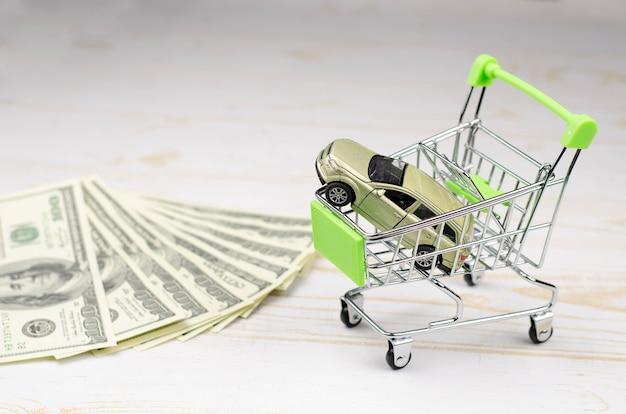 Kleine grüne einkaufskarttrolley mit einem spielzeugauto und 100-dollar-banknoten auf weißem holz