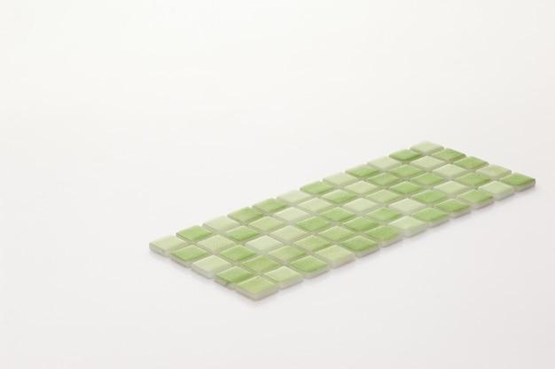 Kleine grüne keramikfliese auf weißem hintergrund, majolika. für den katalog