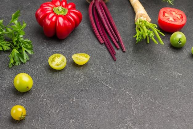 Kleine grüne tomaten, paprika und petersilie, eine halbe rote tomate auf dem tisch. platz kopieren. schwarzer hintergrund. ansicht von oben