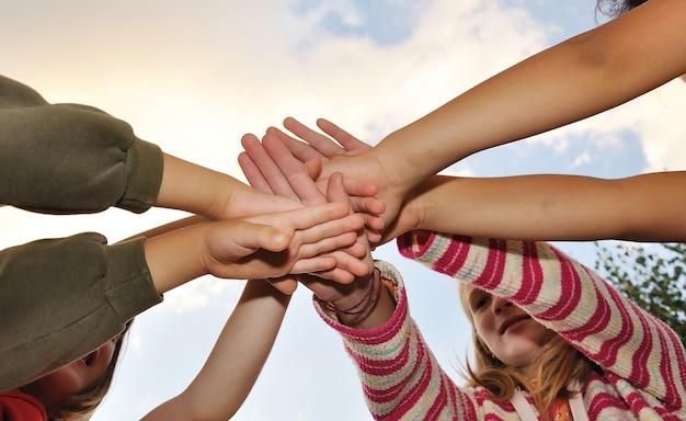 Kleine gruppe glückliche kinder im freien, ihre hände gekreuzt