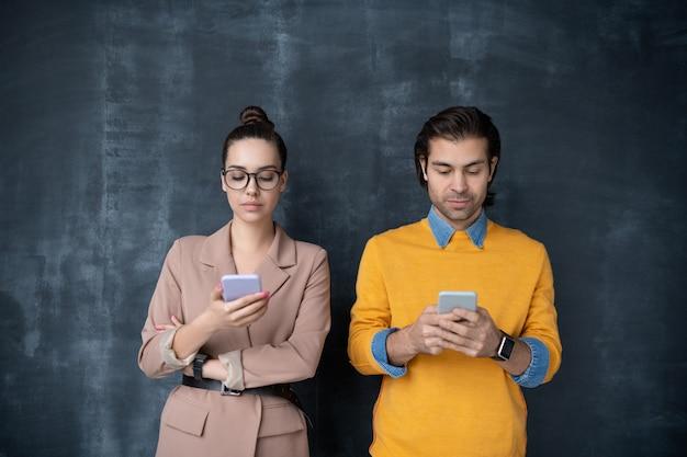 Kleine gruppe junger ernsthafter kollegen in schicker freizeitkleidung, die an der tafel stehen und in ihren mobilen geräten scrollen