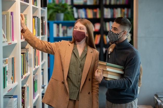 Kleine gruppe junger studenten in masken, die bücher auswählen