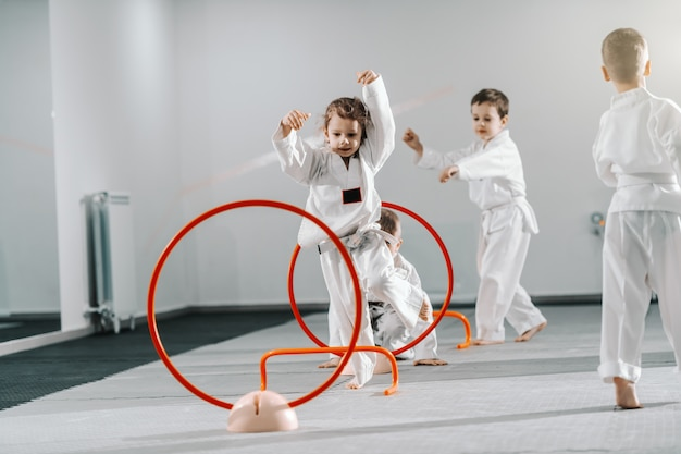 Kleine gruppe kaukasischer kinder in doboks, die taekwondo üben und sich zum treining aufwärmen, während sie barfuß stehen.