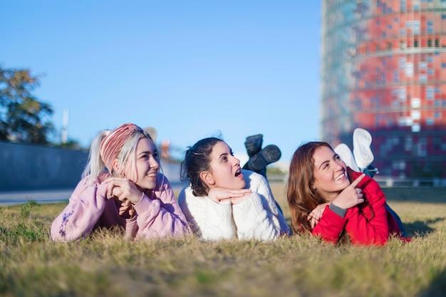 Kleine gruppe schöne mädchen, die auf gras zusammen liegen lachen