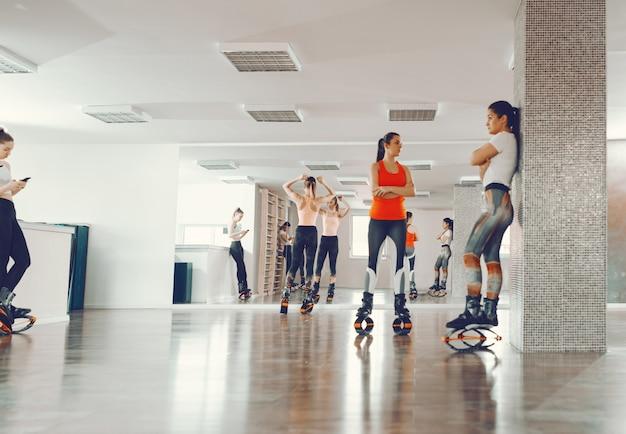 Kleine gruppe sportlicher frauen, die darauf warten, ihren fitnesskurs zu beginnen. sie alle tragen kängurusprungschuhe. ihr körper kann alles.