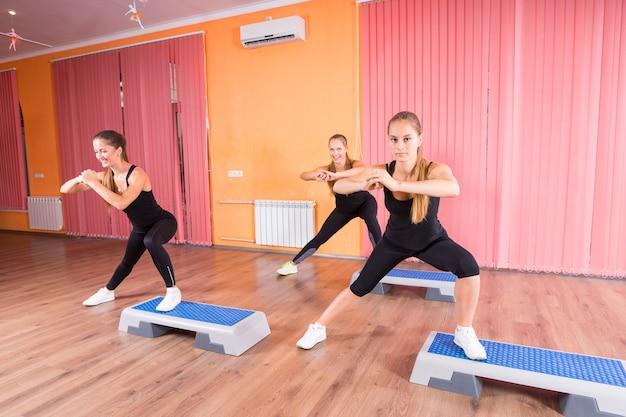 Kleine gruppe von drei jungen frauen, die zusammen im step-aerobic-kurs in einem modernen und farbenfrohen tanzstudio trainieren