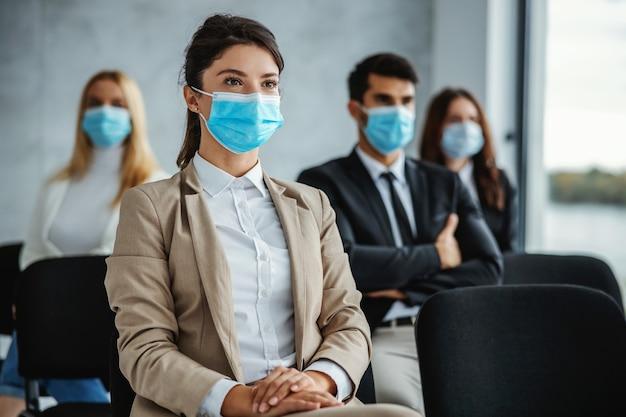 Kleine gruppe von geschäftsleuten mit gesichtsmasken, die auf seminar während des koronavirus sitzen