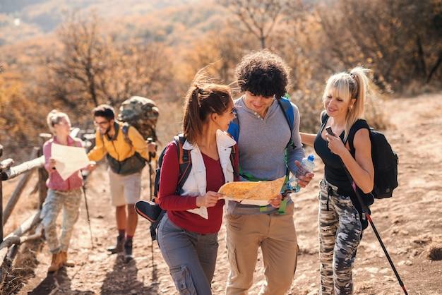 Kleine gruppe von menschen, die wandern und karte betrachten, während sie auf der lichtung im herbst stehen.