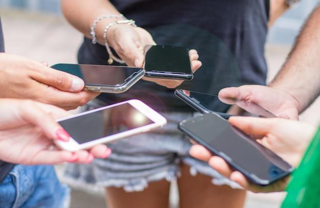 Kleine gruppe von personen, die zusammen mobiltelefone verwendet