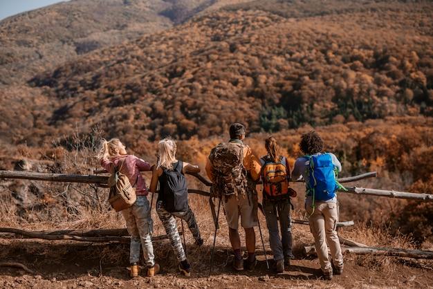 Kleine gruppe von wanderern, die sich auf zaun stützen und schöne aussicht betrachten.