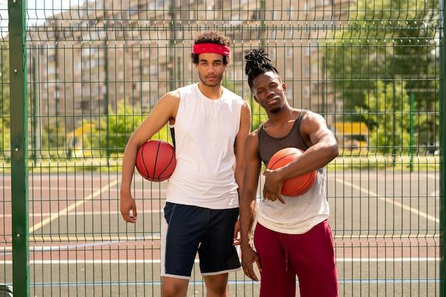 Kleine gruppe von zwei jungen professionellen basketballern in aktivkleidung, die durch den zaun um den hof stehen