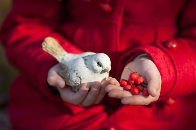 Kleine hände des kleinen kindes der nahaufnahme, die handgefertigten schwarzen weißen vogel der kreativen keramikhandarbeit halten.