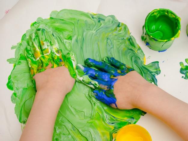 Kleine hände, die mit farben spielen.