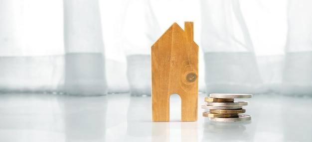 Kleine häuser stehen auf münzstapeln. investitionssparkonzept