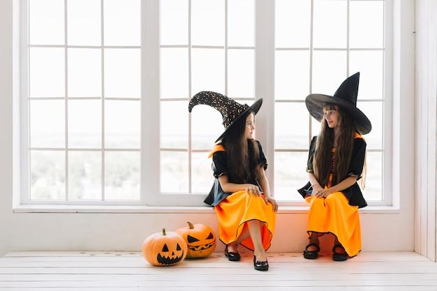 Kleine halloween-hexen, die auf fensterbrett sprechen