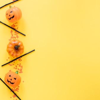 Kleine halloween kürbisse und plastikschläuche in einer linie gelegt