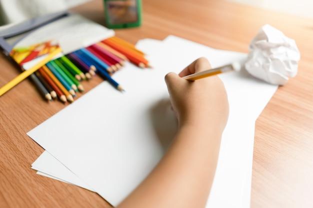 Kleine hand des kinderschreibens auf papier