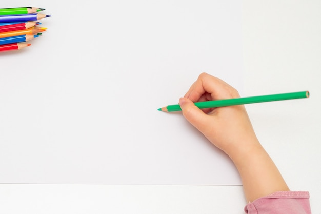 Kleine hand des mädchens, das auf papier zeichnet.