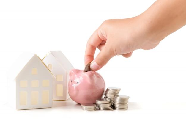 Kleine hand, die münze zum sparschwein legt und geld spart, um neues haus zu kaufen
