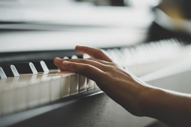 Kleine hand, die musiktastatur aufrechtes klavier spielt