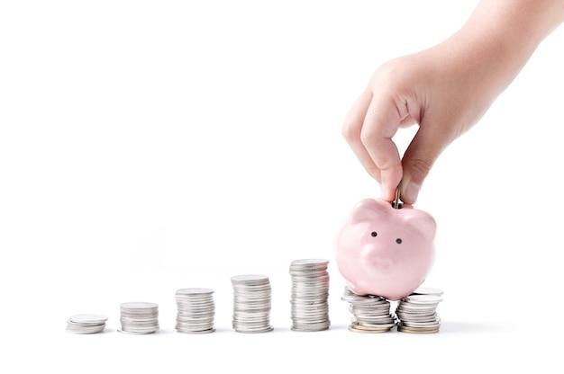 Kleine hand legte münze zum sparschwein