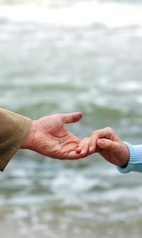 Kleine hand mit einem handschlag auf eine große hand geben