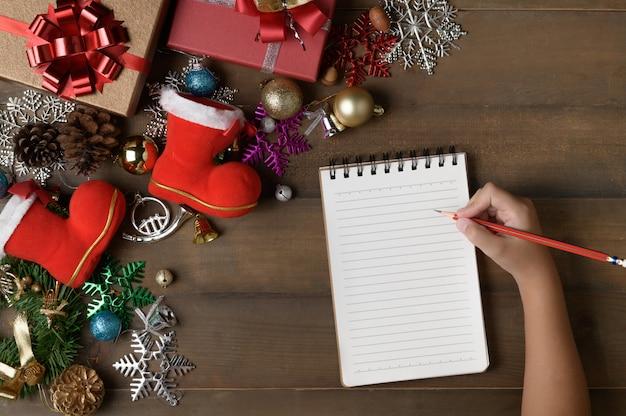 Kleine hand schreiben auf leeres briefpapier mit dekorationen und geschenkboxen