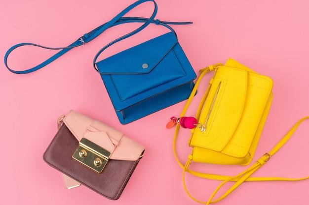 Kleine handtaschenkupplung der frau auf einem hellen rosa hintergrund