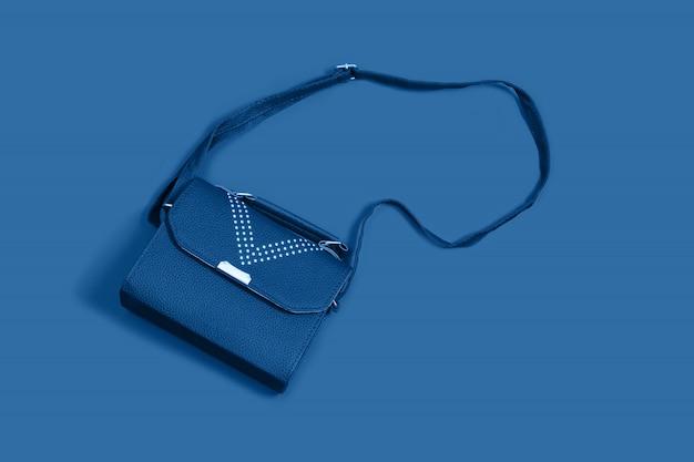 Kleine handtaschenkupplung des frauenleders auf blau. minimalismus in frauensachen.