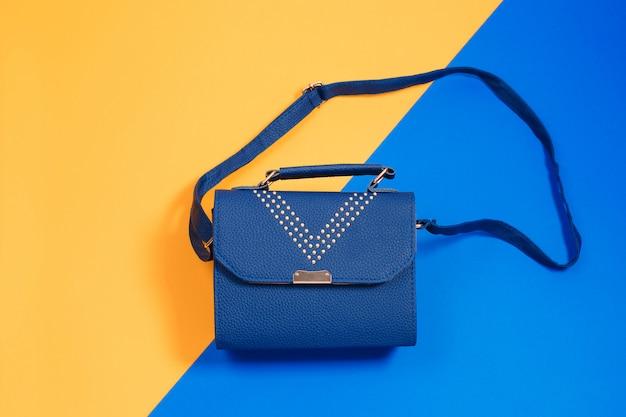 Kleine handtaschenkupplung des frauenleders auf blau und gelb