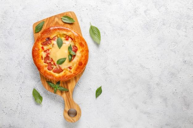 Kleine hausgemachte pizza frisch mit basilikum.
