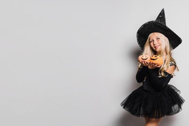 Kleine hexe, die nette jack-o-laternen zeigt