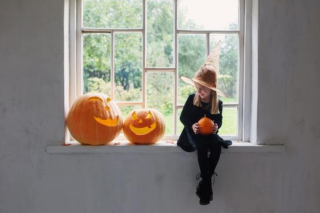 Kleine hexe im schwarzen kleid mit halloween-kürbissen auf der fensterbank