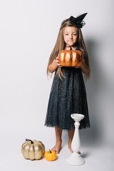 Kleine hexe mit falschem kürbis