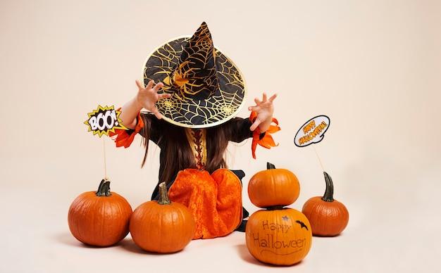 Kleine hexe mit halloween-kürbis