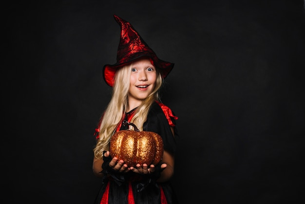 Kleine hexe mit kürbis