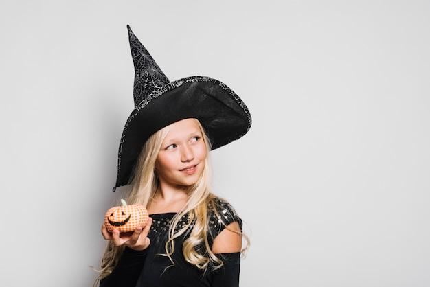 Kleine hexe mit spielzeug jack-o-laterne, die weg schaut