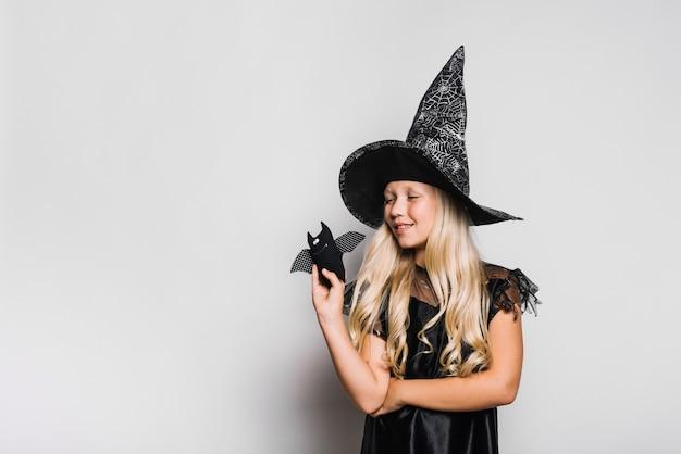 Kleine hexe mit spielzeugfledermaus