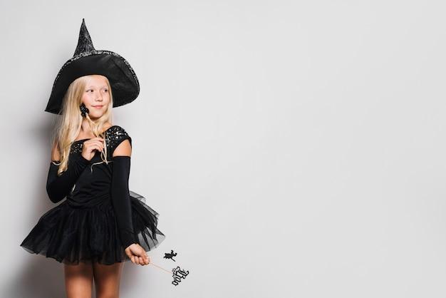 Kleine hexe mit zauberstäben