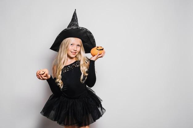 Kleine hexe posiert mit jack-o-laternen