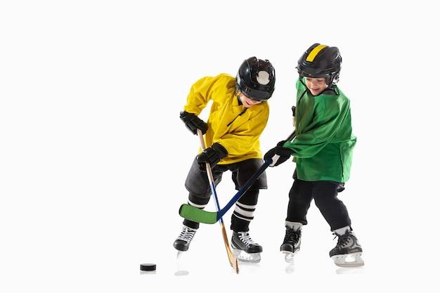 Kleine hockeyspieler mit den stöcken auf eisplatz und weißem studiohintergrund. sportsboys, die ausrüstung und helmübungen tragen. konzept des sports, gesunder lebensstil, bewegung, bewegung, aktion.