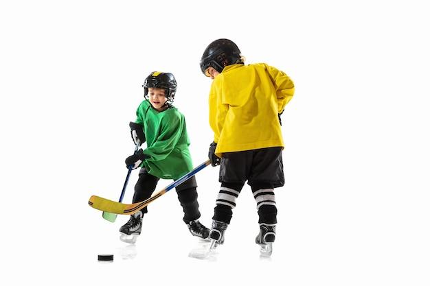 Kleine hockeyspieler mit den stöcken auf eisplatz und weißer studiowand