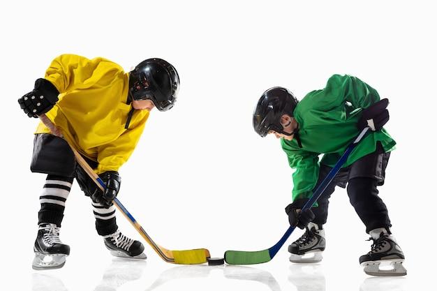 Kleine hockeyspieler mit den stöcken auf eisplatz und weißer wand. sportler mit ausrüstung und helm üben. konzept von sport, gesundem lebensstil, bewegung, bewegung, aktion.