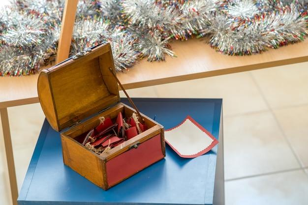 Kleine hölzerne geschenkbox mit roten grußkarten nach innen.