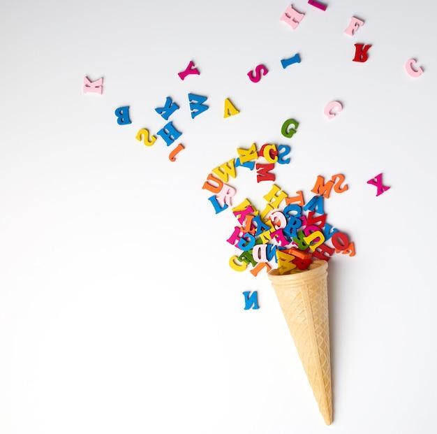Kleine hölzerne mehrfarbige buchstaben des englischen alphabets zerstreuten von einer konischen waffelschale