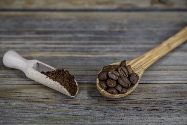 Kleine holzlöffel mit kaffeebohnen und kaffeepulver